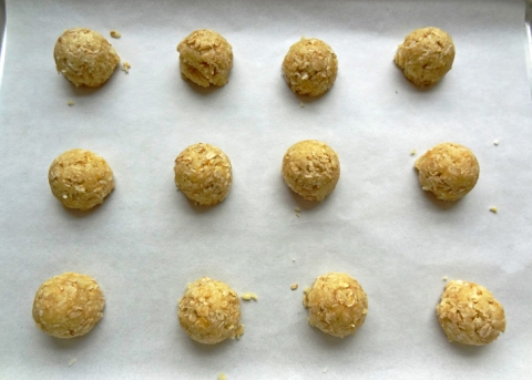 Anzac biscuit dough scooped onto a prepared sheet pan