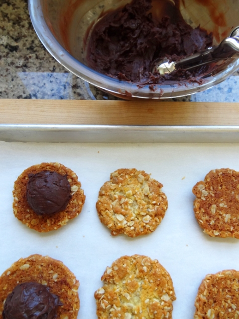 Scooping chocolate-truffle filling onto Anzac biscuits