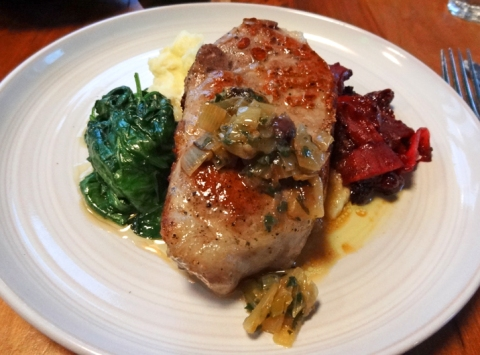 Man-sized pork chop with greens, mashed potatoes, and apple compote