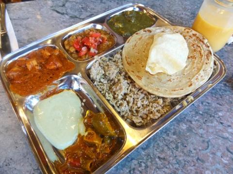 8 Item Thali Platter: Brown rice, flat bread (paratha), lentil wafter (papadum), garbanzo beans, pickles, salad, chicken tikka masala, saag paneer