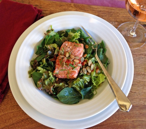 Baked Alaskan sockeye salmon, served over a green salad of red leaf lettuce and baby spinach, finished with chopped chives and toasted pumpkin seeds