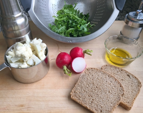 A showcase of organic produce: Cauliflower, freshly ground black pepper, arugula, radishes, sea salt, olive oil, and spelt bread